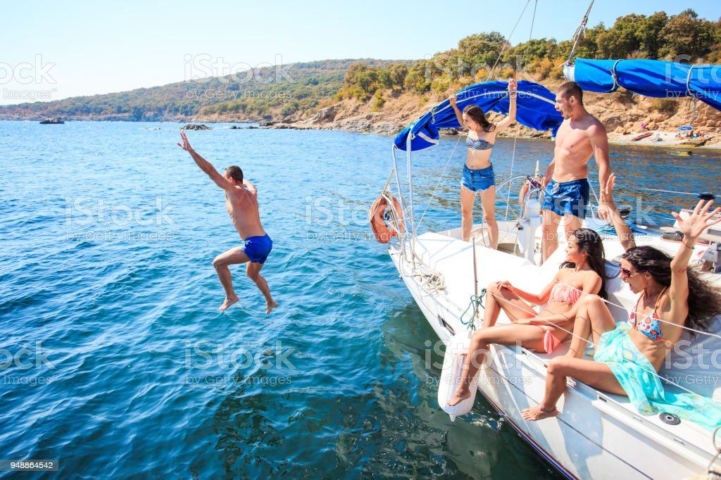 Young people jumping from yacht - fotografia de stock