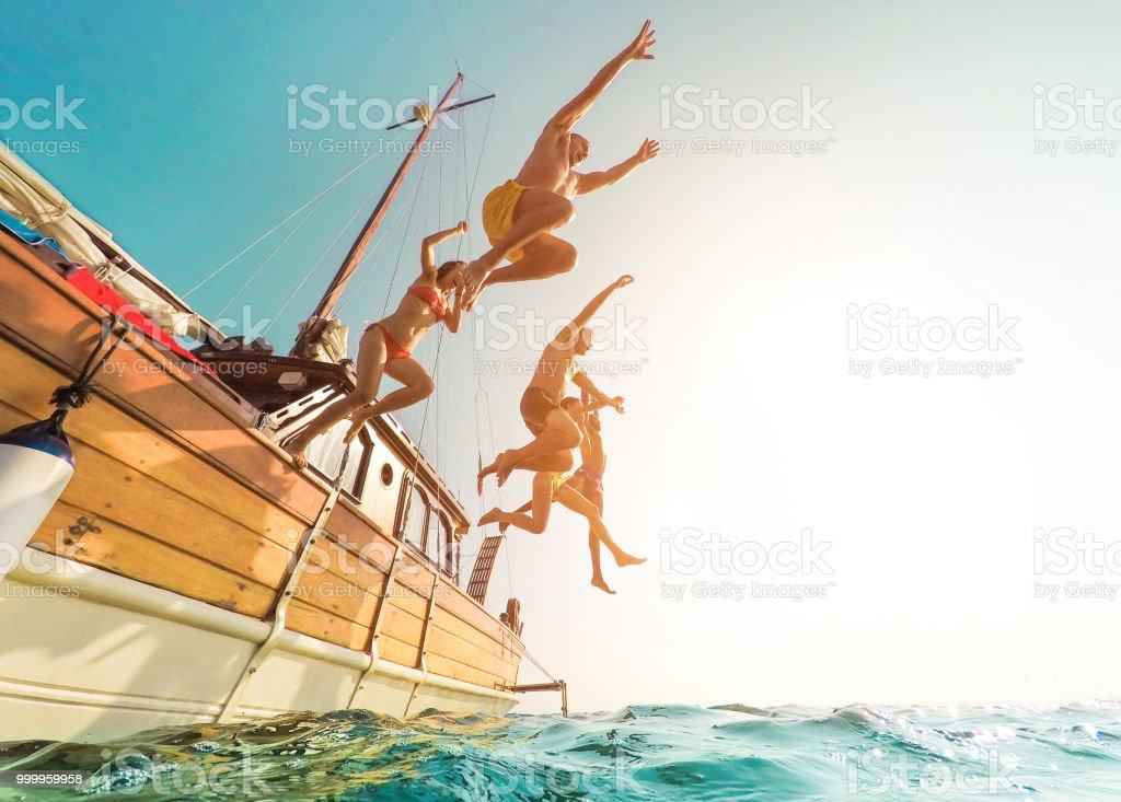 Jovens pulando dentro oceano em dia de excursão de verão - felizes amigos de barco à vela, mergulhar o conceito de juventude e diversão de mar - férias, distorção da lente Fisheye - foco na silhueta de corpos- - foto de acervo