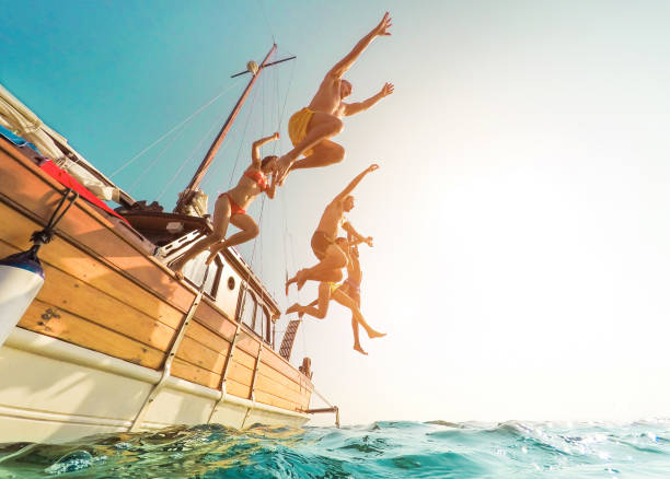 young people jumping inside ocean in summer excursion day - happy friends diving from sailing boat into the sea - vacation, youth and fun concept - focus on bodies silhouette - fisheye lens distortion - vacations stock pictures, royalty-free photos & images