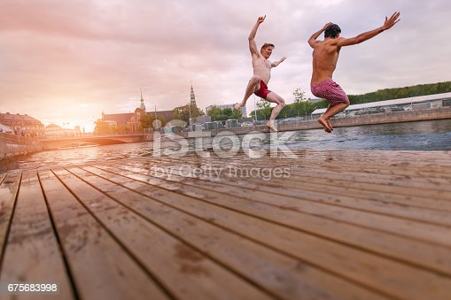 istock Young people jumping into lake in city 675683998