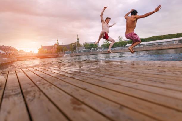 ungdomar hoppar i sjön i staden - flod vatten brygga bildbanksfoton och bilder