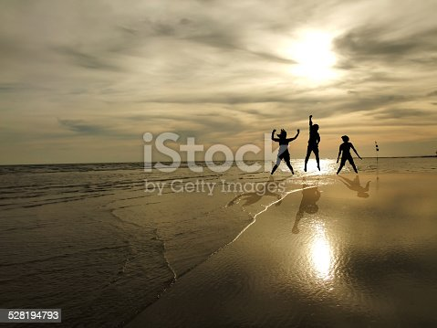 istock young people jumping on the beach with sunset background 528194793