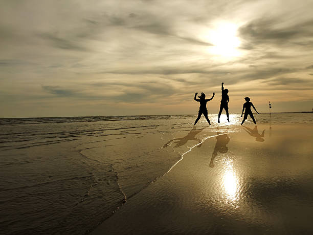 young people jumping on the beach with sunset background stock photo