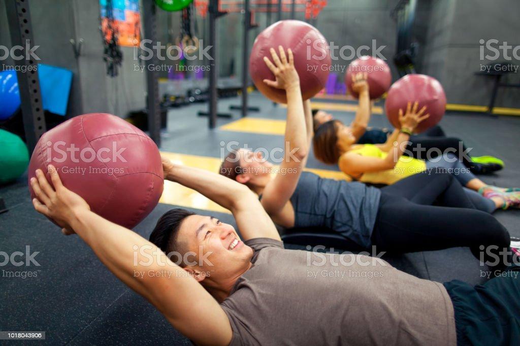 Junge Menschen heben gymnastikball in Übung – Foto