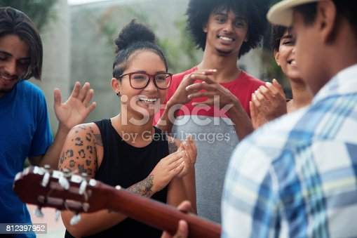istock Young people listening to a concert of a muscian 812397952