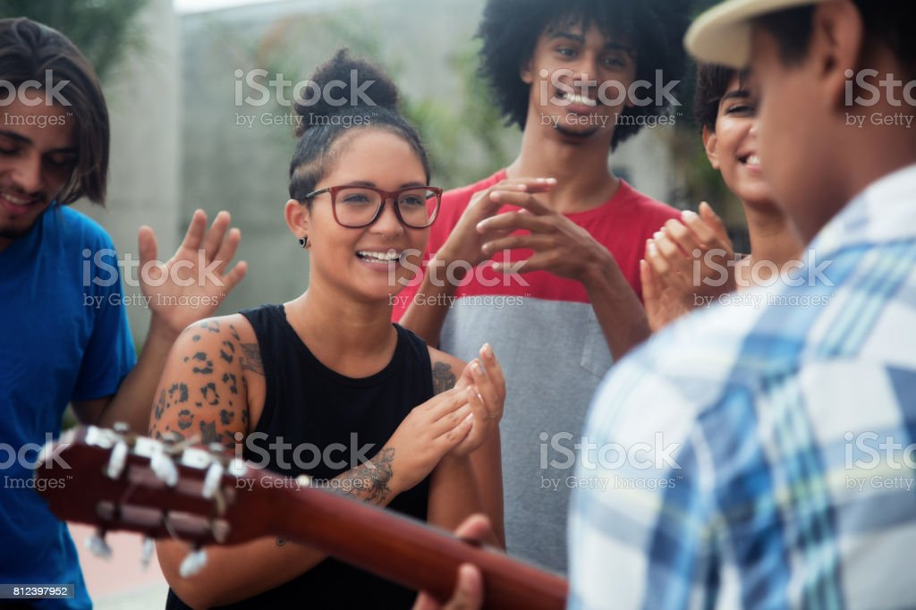Young people listening to a concert of a muscian stock photo