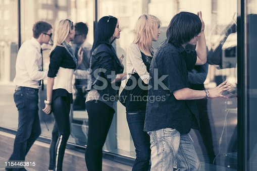 Young fashion men and women looking through the mall window