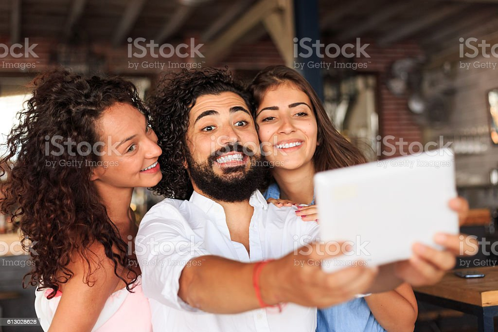 Young people making selfie at bar with digital tablet stock photo