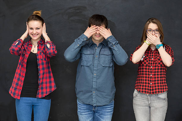 Young People making three wise monkey sign Young People Man and Women making three wise monkey gesture - see no evil, hear no evil, speak no evil - on black Board background hear no evil stock pictures, royalty-free photos & images