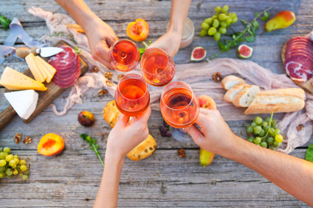Young people making toast at picnic with rose wine stock photo