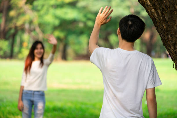 young people, man and woman greeting or saying goodbye by waving hands in the park. - disconnect stock pictures, royalty-free photos & images