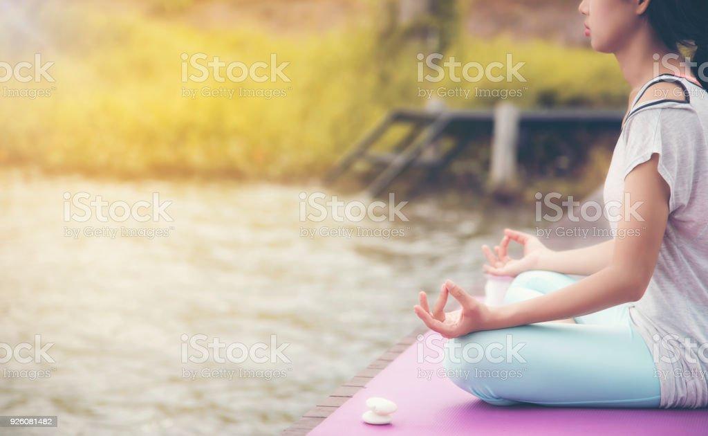 Junge Menschen meditieren am Wasser auf einer Holzbrücke für eine gute Gesundheit. – Foto