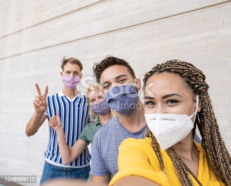 Young people meet and take a selfie - Multiracial friends wearing protective face masks - Focus on the face of the african woman