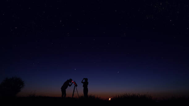 Young people observing the night sky stock photo