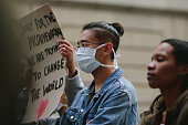 Group of young people on a silent protest in the city. Man wearing a protection face mask participating in a strike.