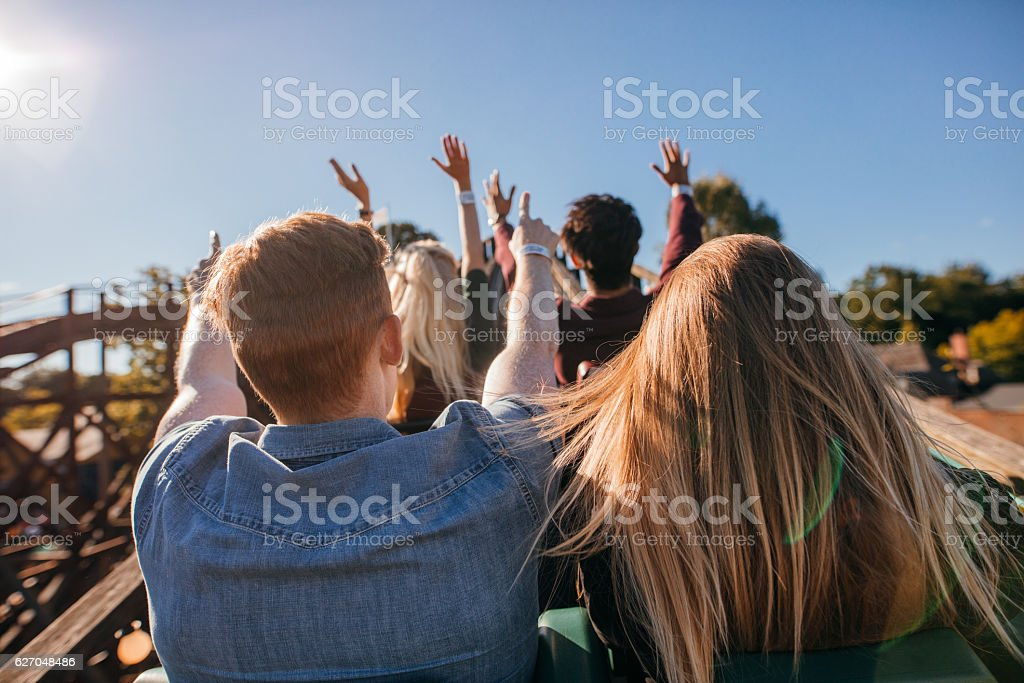 Young people on a thrilling roller coaster ride stock photo