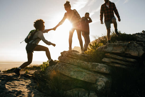 Young people on mountain hike at sunset Group of hikers on a mountain. Woman helping her friend to climb a rock. Young people on mountain hike at sunset. hiking stock pictures, royalty-free photos & images