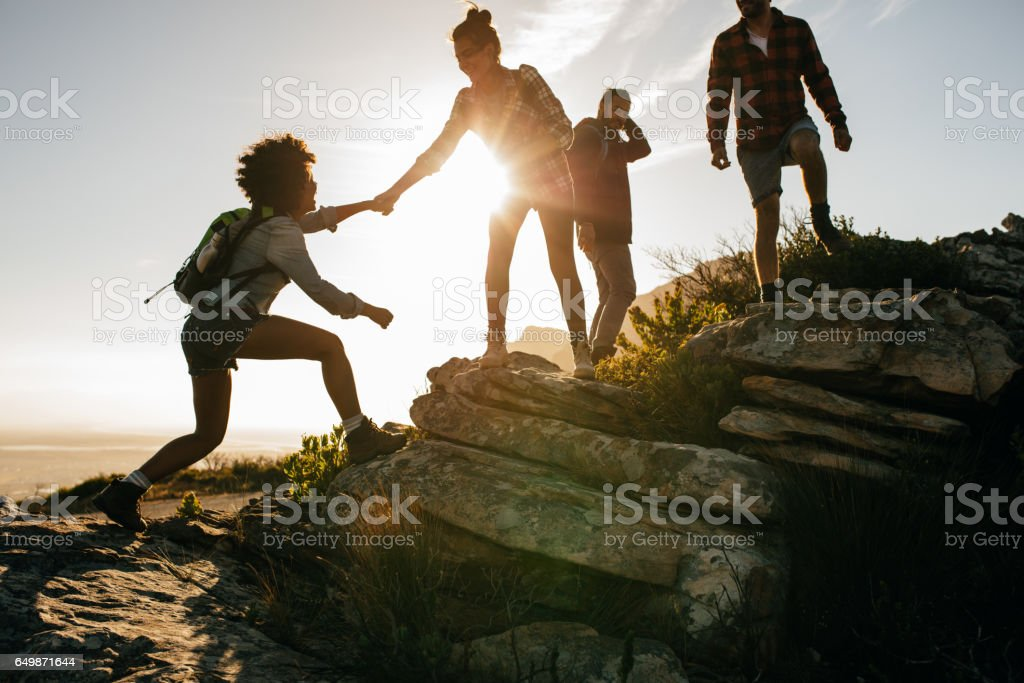 Young people on mountain hike at sunset stock photo