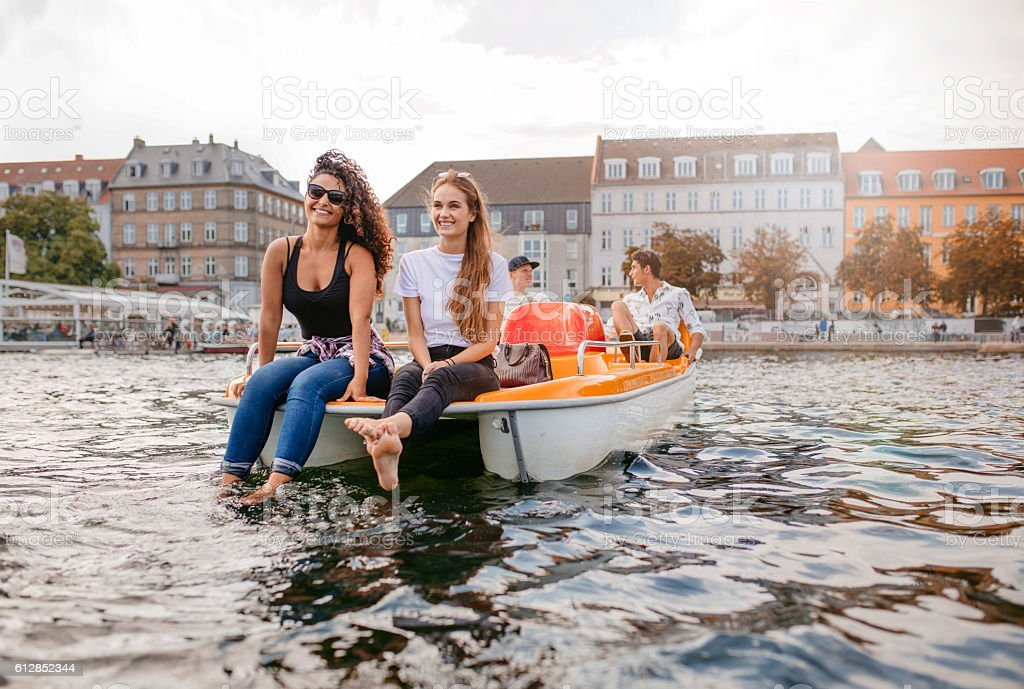 Young people on pedal boat in lake - foto de stock