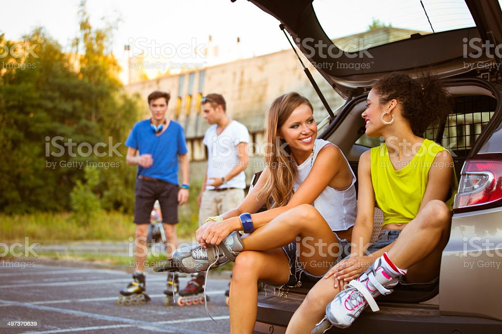 Young people on rollerblades Young people resting after rollerblading. Focus on two girls sitting in a back of van with their boyfriends standing in the background. 20-24 Years Stock Photo