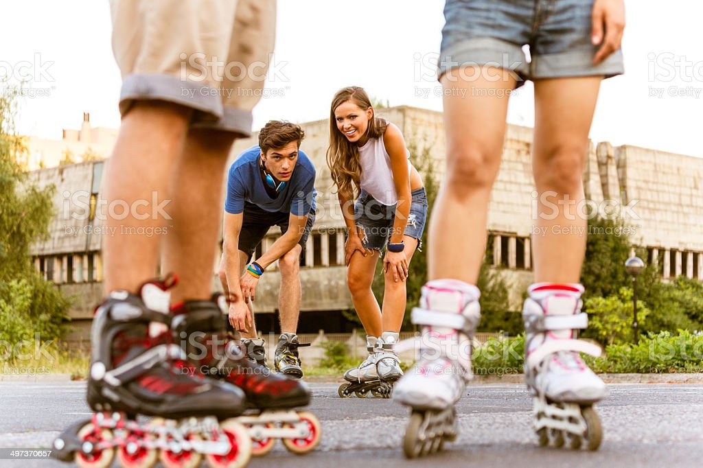 Young people on rollerblades Group of happy young people rollerblading together. Focus on the couple in the background. 20-24 Years Stock Photo