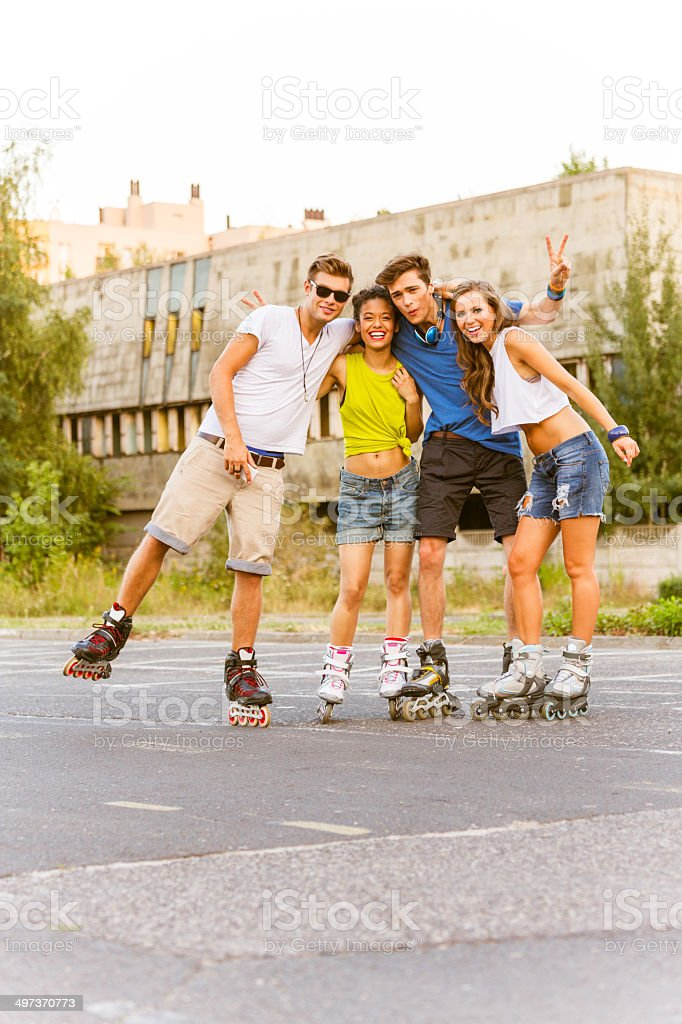 Young people on rollerblades Group of happy young people rollerblading together, smiling at the camera. 20-24 Years Stock Photo