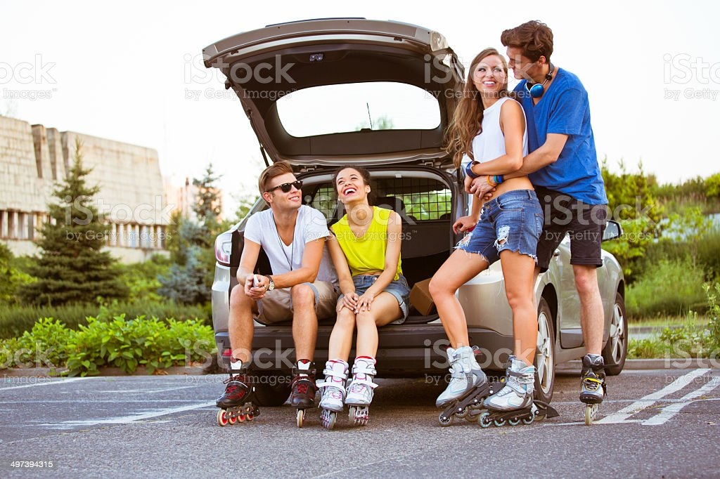 Young people on rollerblades Two young happy couples resting after rollerblading. 20-24 Years Stock Photo