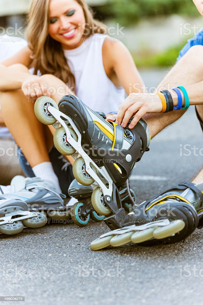 Young people on rollerblades Friends sitting on tarmac and tying rollerblades. Close up of legs. 20-24 Years Stock Photo