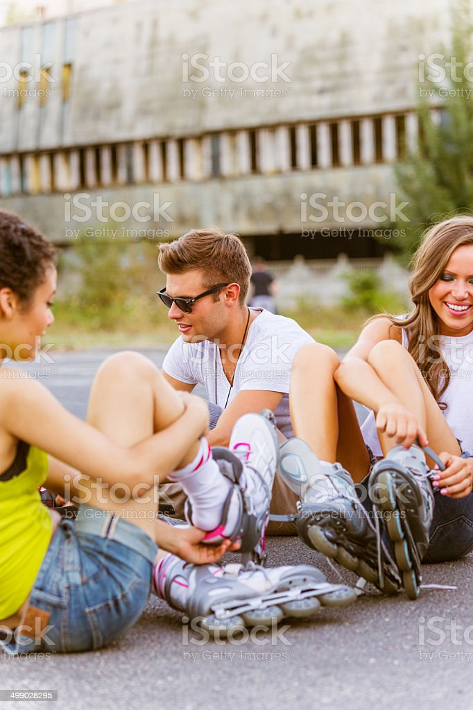 Young people on rollerblades Friends sitting on tarmac and tying rollerblades. 20-24 Years Stock Photo