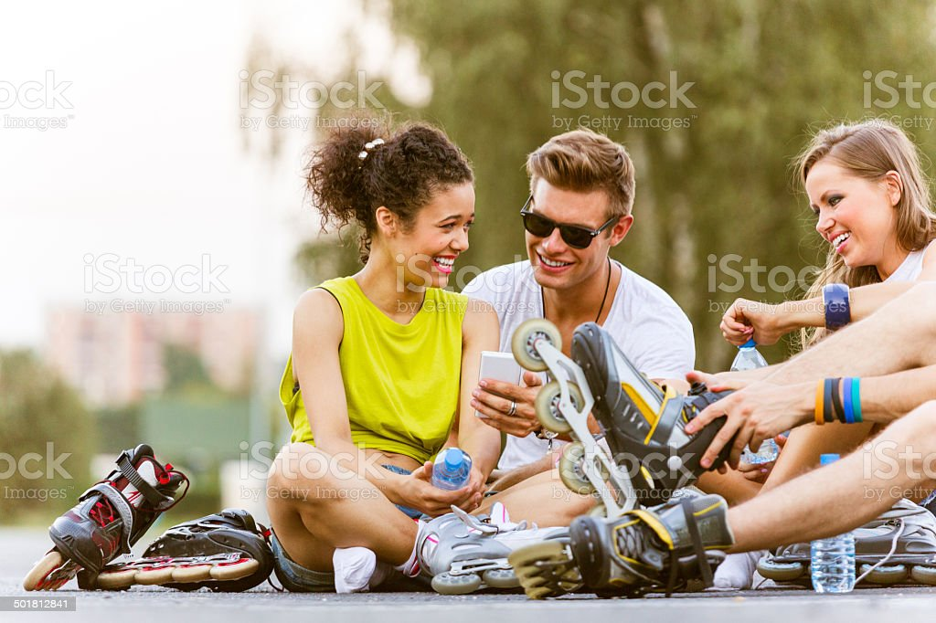 Young people on rollerblades Young people resting after rollerblading, sitting on the tarmac and talking. The boy holding smart phone in hand. 20-24 Years Stock Photo