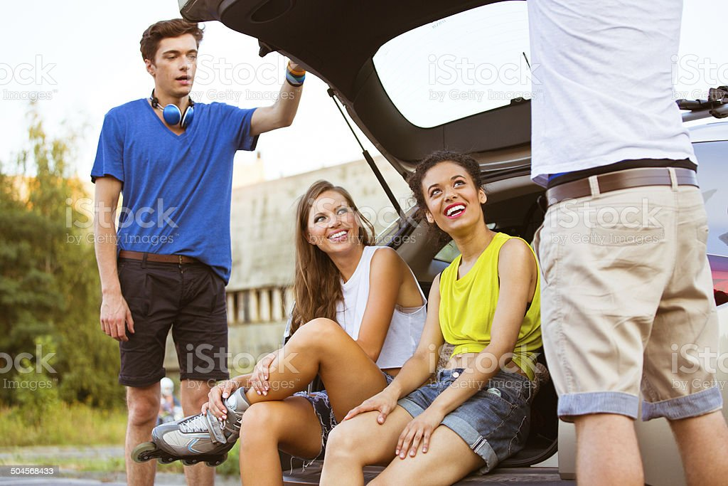 Young people on rollerblades Happy friends resting after rollerblading. Two young women sitting in a car trunk. 20-24 Years Stock Photo