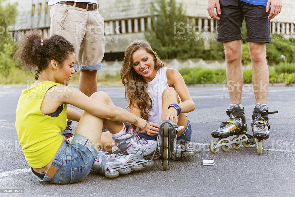 Young people on rollerblades Two young women sitting on tarmac and tying rollerblades with guys standing behind them. 20-24 Years Stock Photo