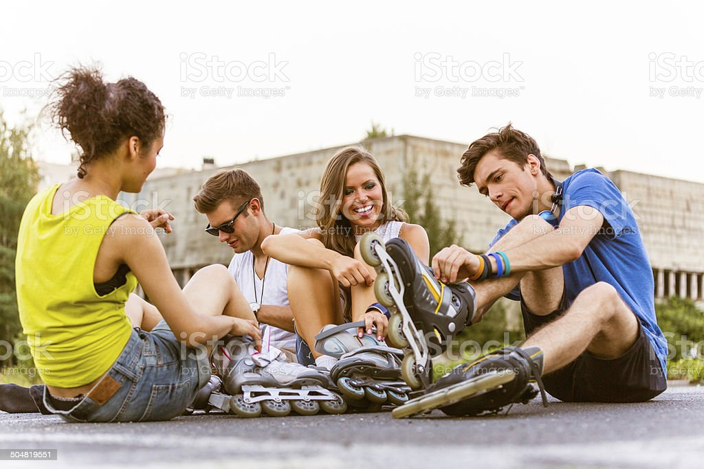 Young people on rollerblades Four friends sitting on tarmac and tying rollerblades. 20-24 Years Stock Photo