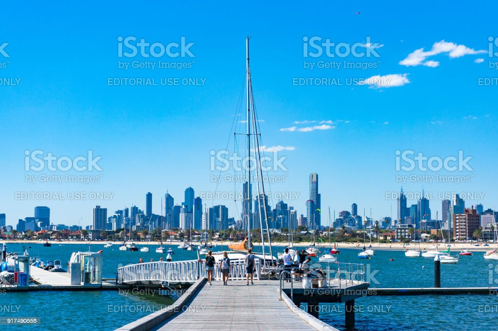 Young people on St. Kilda pier with Melbourne cityscape on the background stock photo