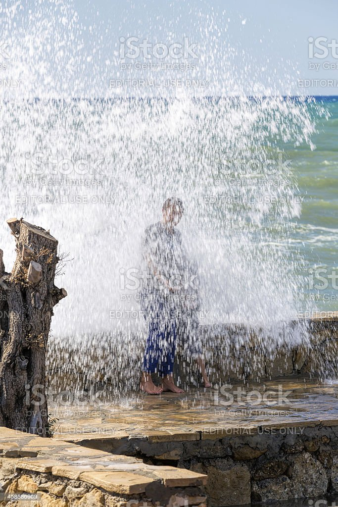Young people on the pier against big wave royalty-free stock photo