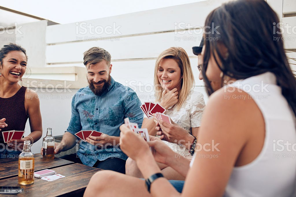 Group of friends sitting at a wooden table and playing cards. Young...