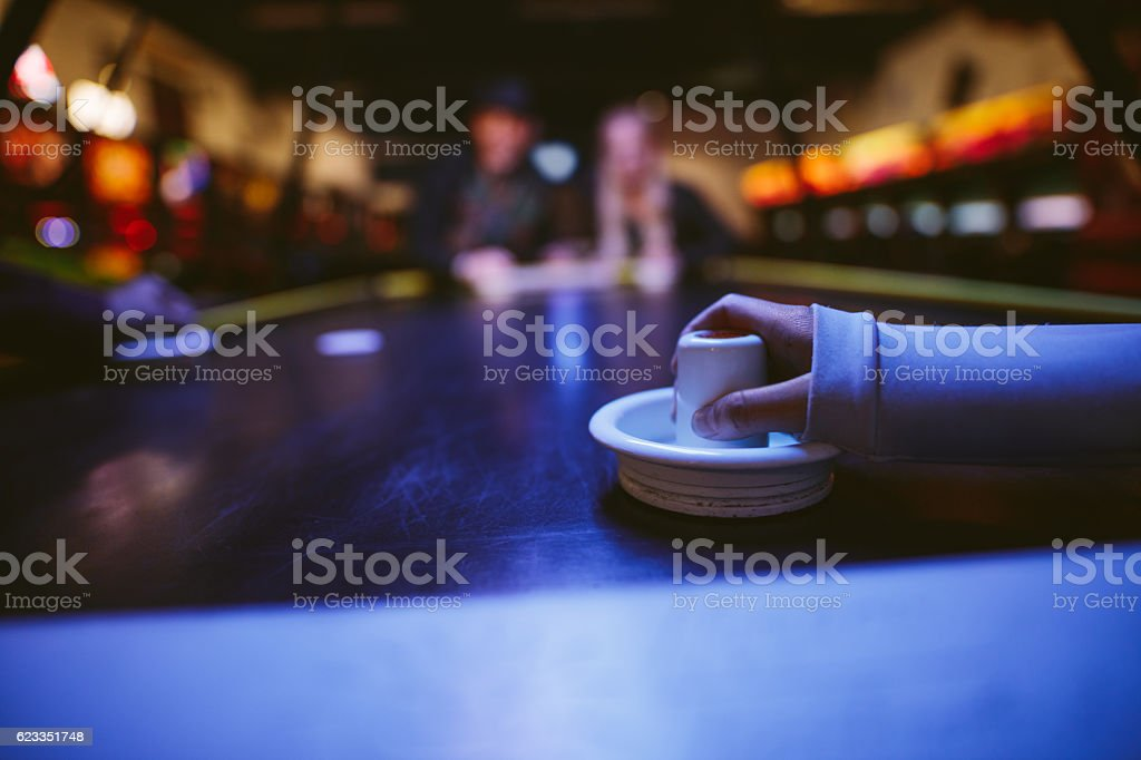 Young people playing air hockey stock photo