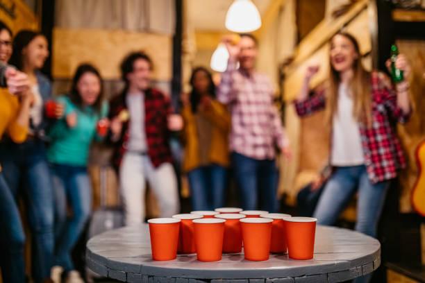jonge mensen die bierpong in herberg spelen - beirut stockfoto's en -beelden
