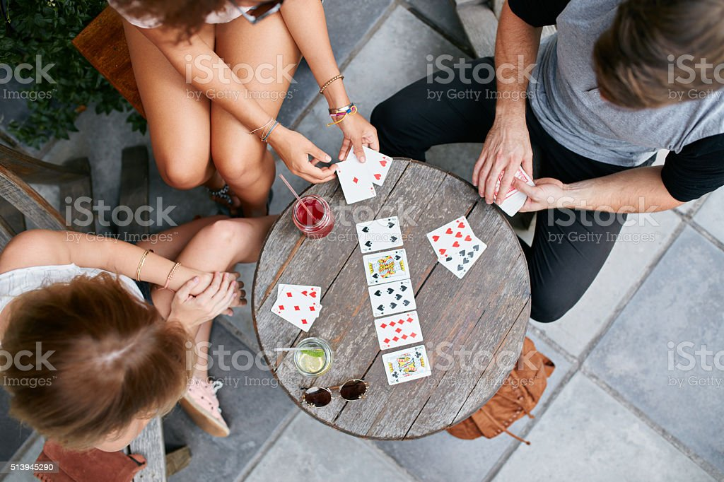 Young people playing cards at sidewalk cafe stock photo