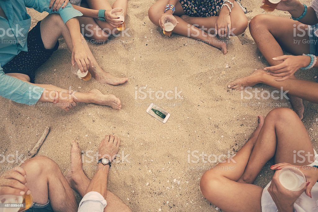 Young people playing spin the bottle at the beach stock photo