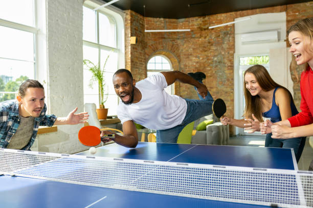 young people playing table tennis in workplace, having fun - table tennis stock pictures, royalty-free photos & images