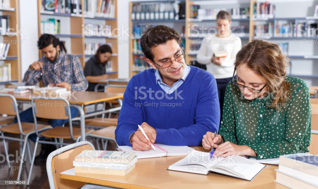 Young people reading and making notes while preparing for exam in...