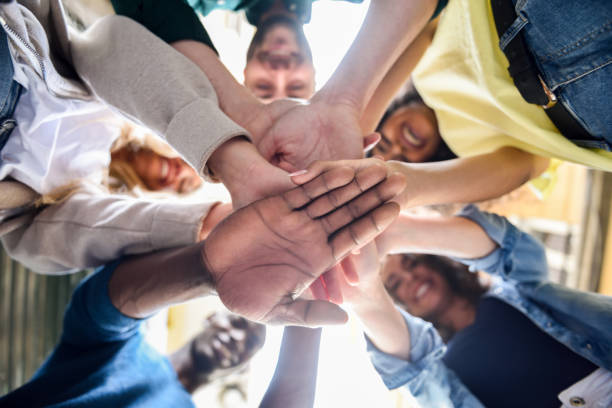 Young people putting their hands together. stock photo