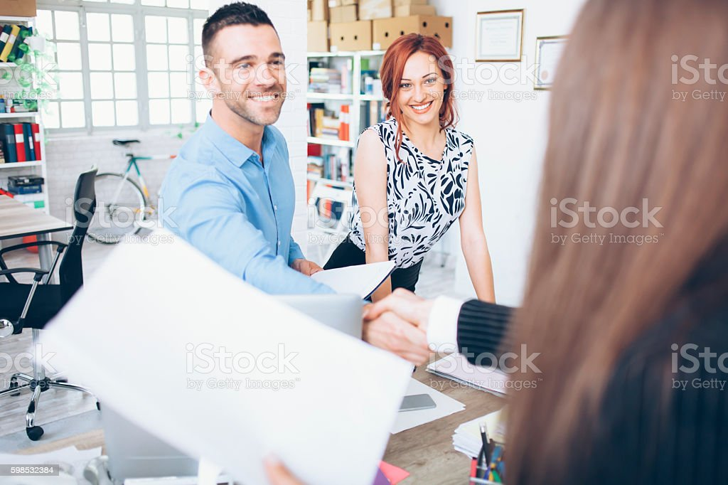 Young people in handshake at modern office. One man and two women in...