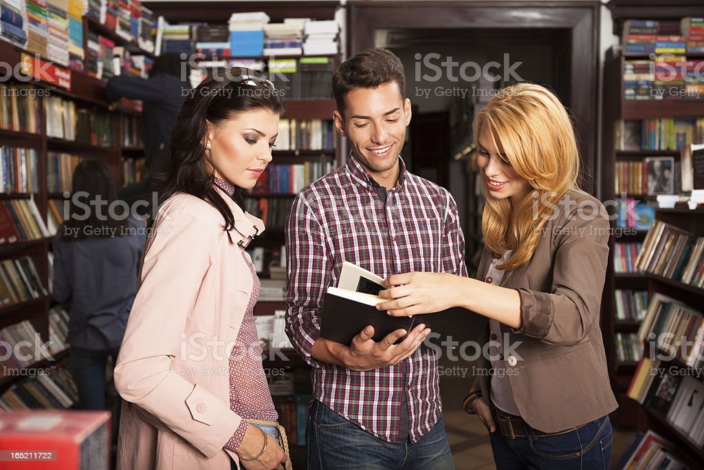 young people reading a book in library royalty-free stock photo