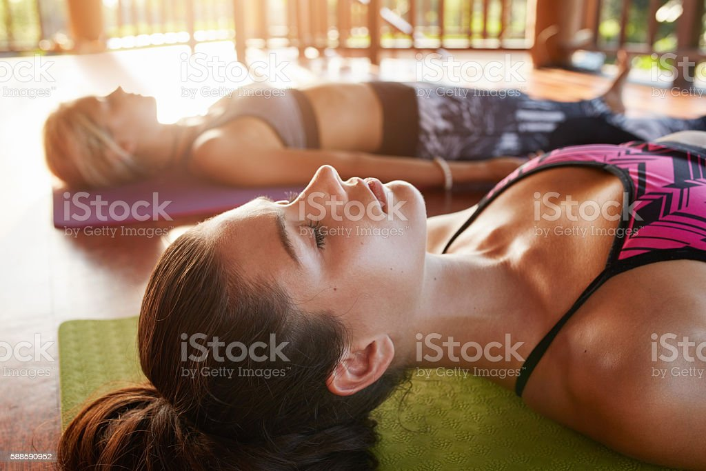 Young people relaxing in savasana pose at yoga class stock photo