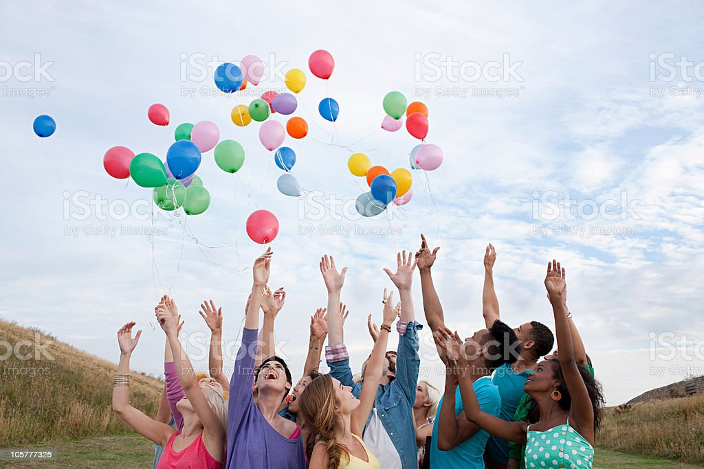 Young people releasing balloons stock photo