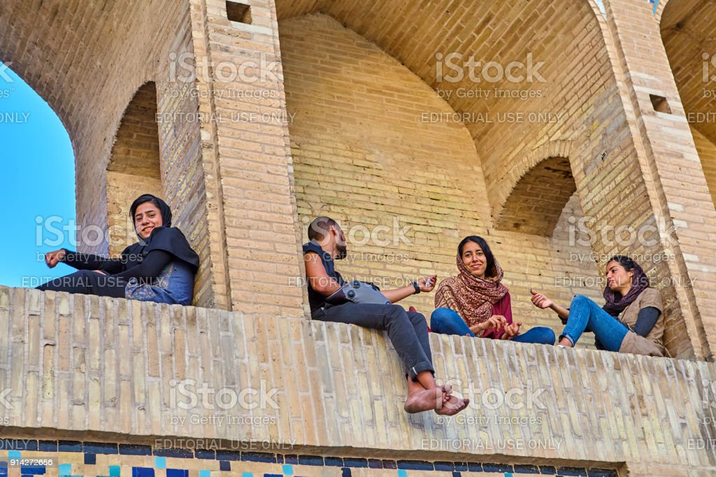 Young people rest in arched niches of bridge, Isfahan, Iran. stock photo