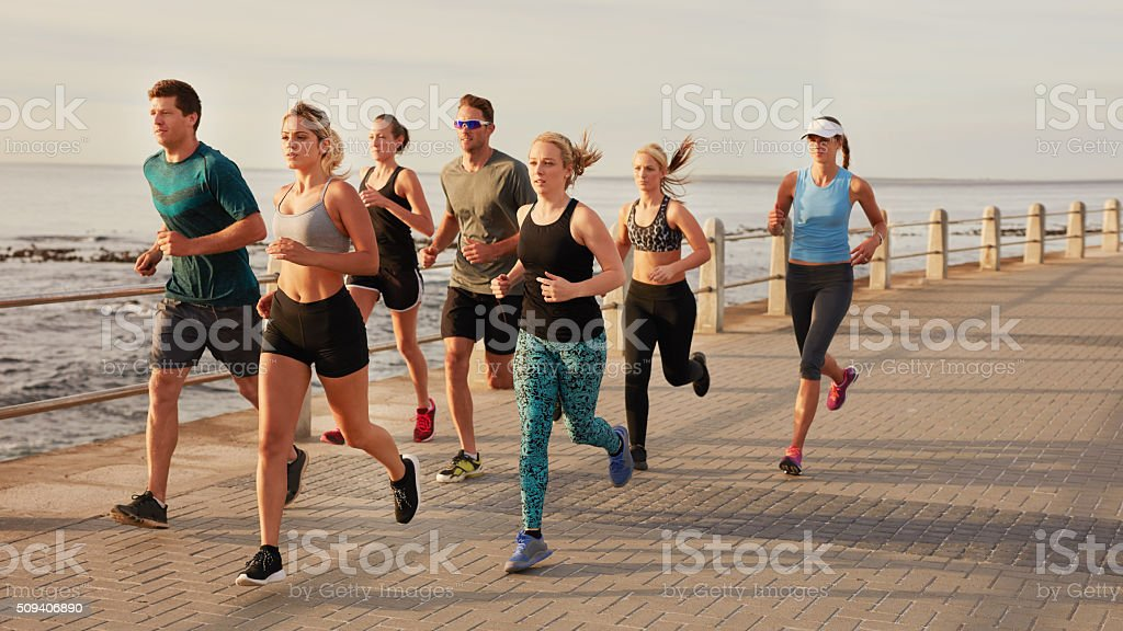 Young people running along beach boardwalk stock photo