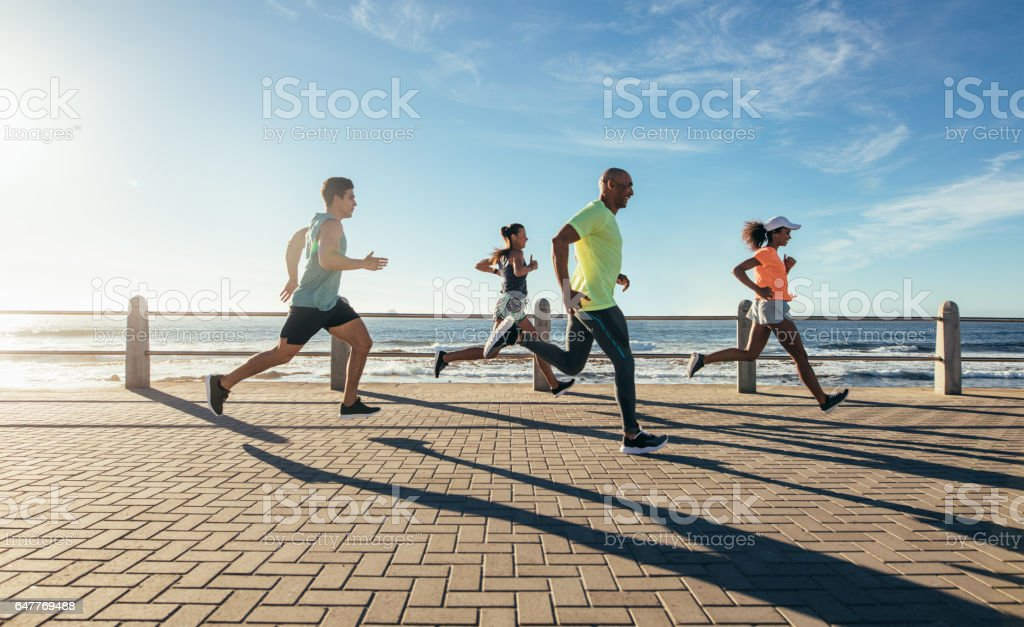Young people running along seaside stock photo